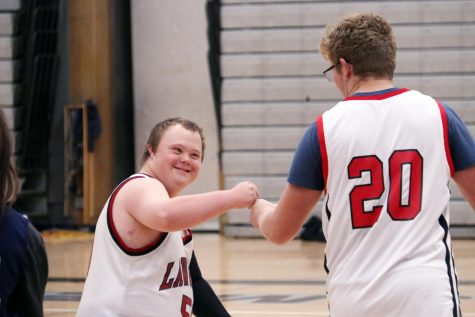 "Spreading the love, junior Dylan Gillespie fist bumps Sky Wilkerson during the Unified Sports basketball game. Although Gillespie worked hard for the team, he confesses that he took a backseat to the real stars of the show. ""I just gave them the ball and they did all the work,"" said Gillespie. ""It was fun to see them all happy and have the experiences they don't usually get to have."""