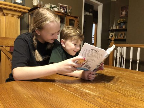 "Helping with her brother Liam, sophomore Kenna McNally reads ""Hamlet and Cheese. While her parents work, McNally is one of many high school students who is also helping care for younger siblings."