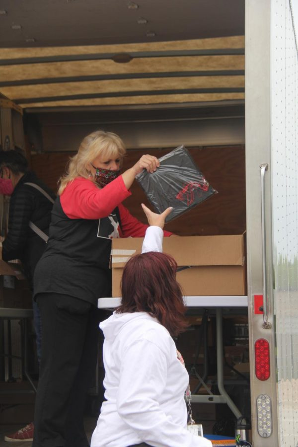 Tracy Urish activities secretary, hands a hand and gown to counselor Lori Stussie as seniors picked up caps and gowns on Thursday. The process was staged out of a truck.