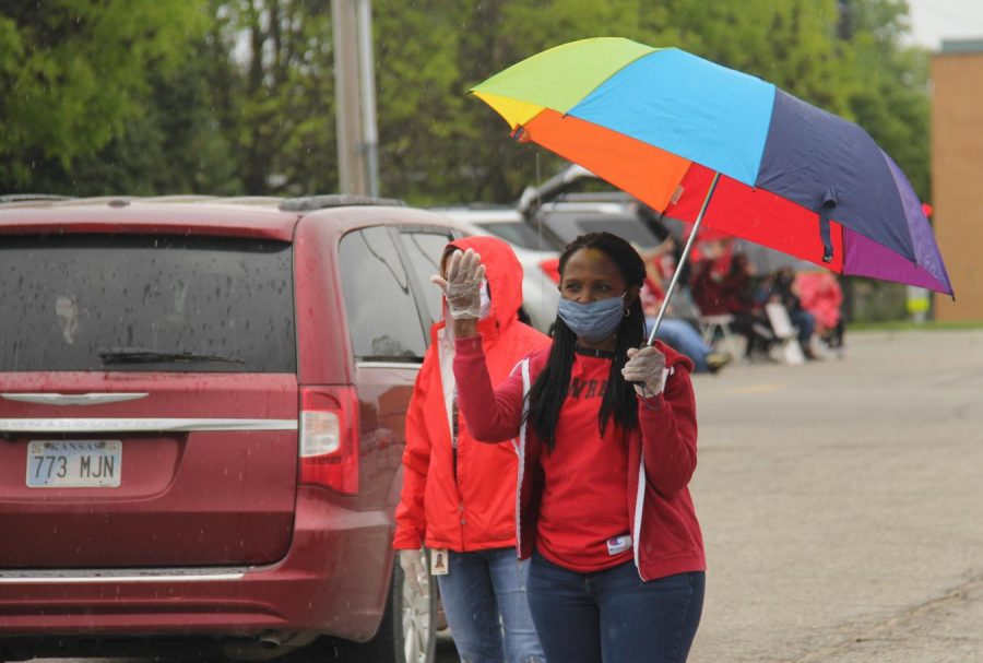 Lynisha Thomas, LHS social worker, directs traffic as students pick up caps and gowns from LHS on Thursday.