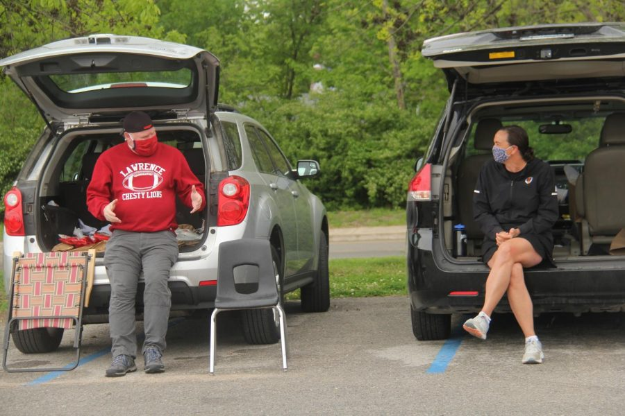 Math teacher Greg Farley talks to science teacher Marci Leuschen as seniors pick up caps and gowns from LHS. Teachers were invited to celebrate seniors as they arrived at the drive-through event but had to wear masks and stay at least six feet apart.