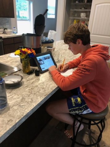 Freshman Samuel Cohen takes notes during online class in his kitchen. Students learn from home because of the ongoing coronavirus pandemic