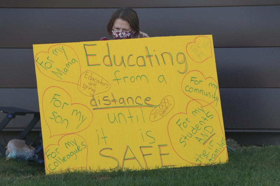 An educator at the PAL-CWA led teach-in talks to her students while sitting behind a sign protesting the school board's decision to push ahead with the transition to hybrid learning.