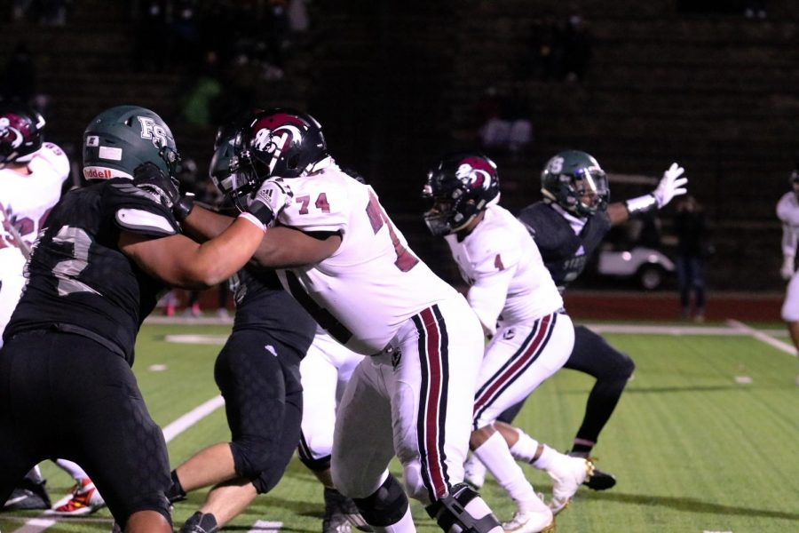 With full force, junior Noah Smith holds back a Free State player so his teammates can complete a pass.