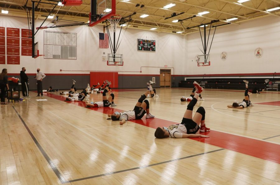 Members of the girls basketball team warm up at a distance while wearing masks after school. The Kansas State High School Activities Association is allowing the season to continue with a few limitations but opted against most drastic limits in games.