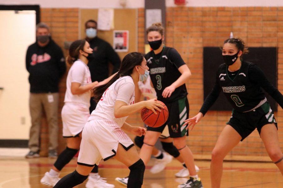 Pushing down the court, junior Layla Harjo dribbles towards the basket.