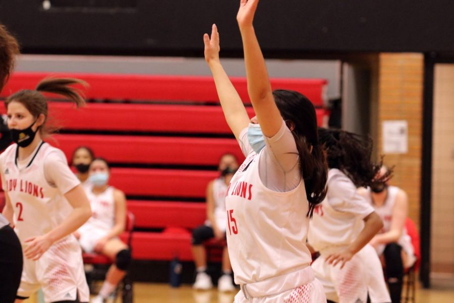 Arms up, junior Layla Harjo tries to protect the basket from another Free State score.