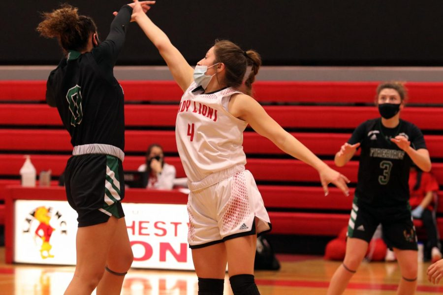 In the air, sophomore Hailey Ramirez swats the ball away from Free State player #0.