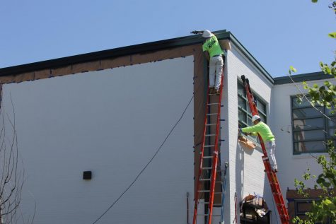 Painters paint the courtyard walls white at LHS in preparation for a large mural, which will be painted this summer.