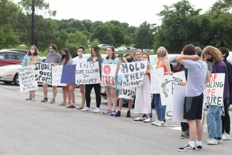 Students stand outside the district holding signs calling for action on sexual assault in schools at the June 28 board meeting.