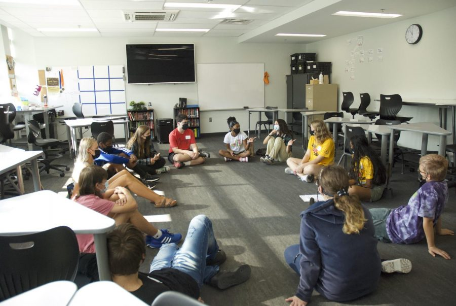 Sitting in a circle, a group of students introduce themselves to one another.