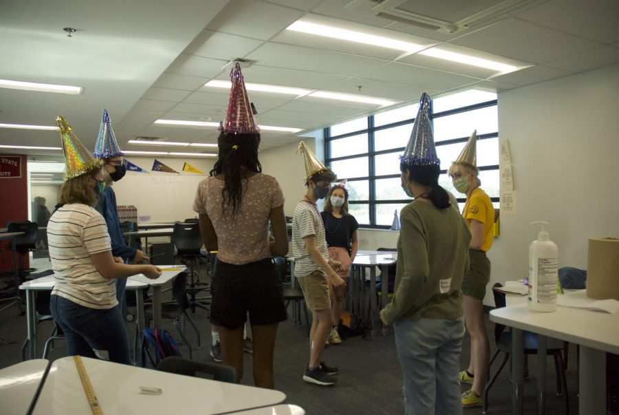 While wearing festive hats, a group of students play a get-to-know-you game.