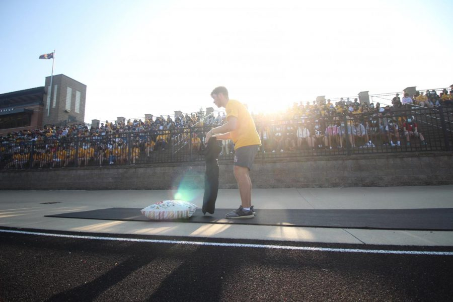 As part of a relay race, a Link Crew member removes and replaces a pillowcase.