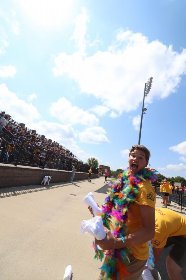 With a t-shirt in each hand, senior Ashton Rapp opens his mouth wide.