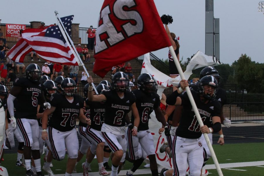 Running in, senior Evan Bannister leads the football team through the banner to kickoff the 2021 season.