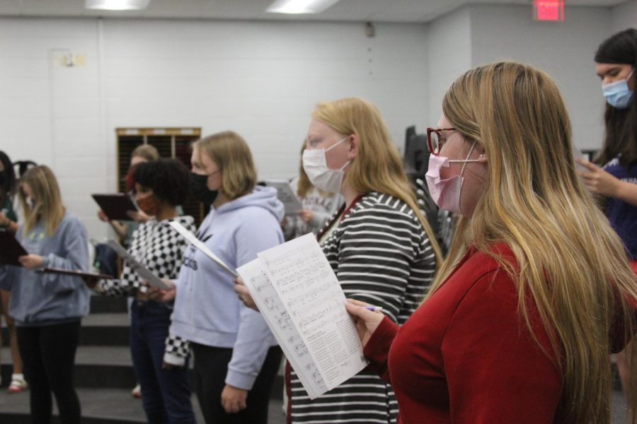 Students practice their choir selections, with masks, before the fall concert.